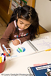Education preschoool children ages 3-5 art activty girl writing her name on drawing of the planet earth vertical
