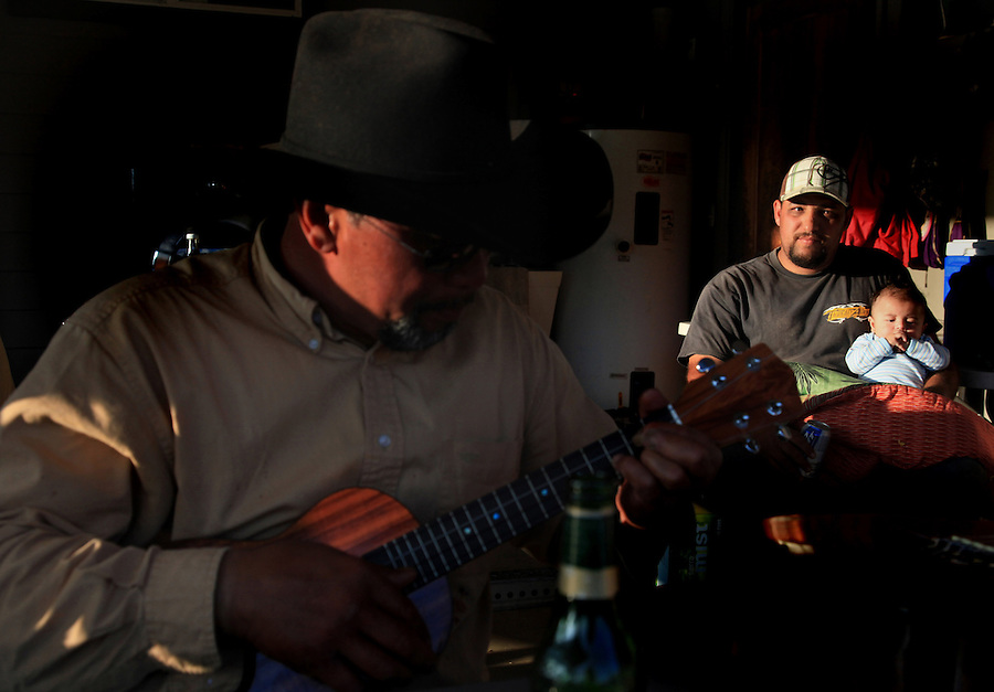 """Bernard Ho'opai plays his ukelele and sings during a post-branding party at his home in Waimea, Hi.  Behind him is his son-in-law, Wilton Camara and his grandson, Payton.  The Ho'opai family are well-known for their musical ability and one of them inevitably plays music whenever friends and family get together.  The Paniolo music is a mixture of Hawaiian music and Mexican music brought over by the vaqueros almost two centuries ago. """"When we were growing up, my mom and dad played a lot of music at home, at parties.  Every since that, it's been planted in like the Paniolo life,"""" says brother Kimo Ho'opai who also plays music and sings whenever there is a gathering."""