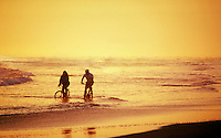 Couple riding bikes in the surf.