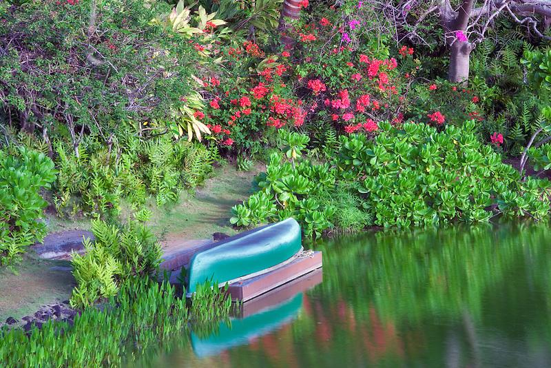 Pond with canoe and garden at Na Aina Kai Botanical Gardens. Kauai, Hawaii