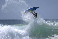 A surfer flipping on top of a wave