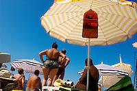 Sunbathers sitting on sun beads looking at the sea. Piran , Slovenia