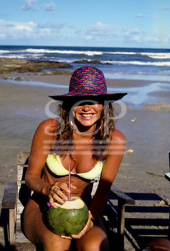 Olivenca, Bahia State, Brazil. Girl in a yellow bikini and purple straw hat drinking from a fresh coconut on the beach.