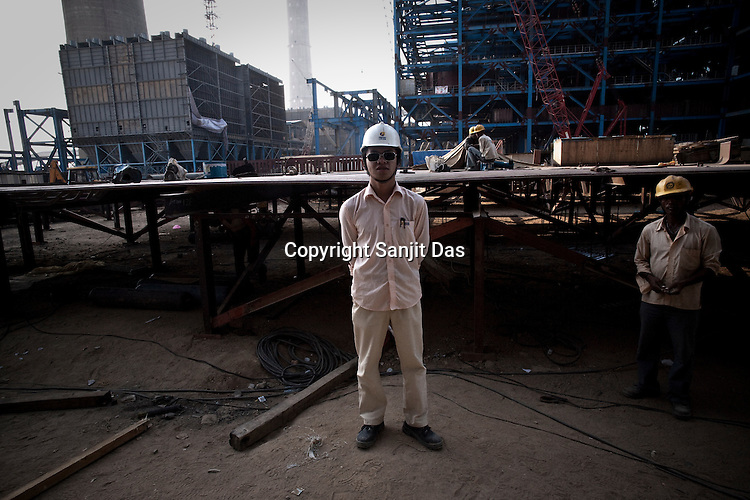 A Chinese engineer from Sepco is seen at the construction site of the Adani Power plant of 4620 MW capacity in Mundra port industrial city of Gujarat, India. Indian power companies have handed out dozens of major contracts to Chinese firms since 2008. Adani Power Ltd have built elaborate Chinatowns to accommodate Chinese workers, complete with Chinese chefs, ping pong tables and Chinese television. Chinese companies now supply equipment for about 25% of the 80,000 megawatts in new capacity.