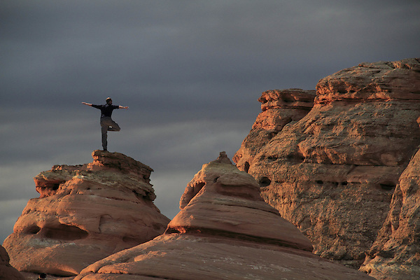 Man balancing in Arches National Park at sunrise, Moab, Utah, USA. .  John offers private photo tours in Arches National Park and throughout Utah and Colorado. Year-round.