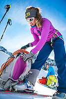 The Ortler Group in northern Italy is a popular region for spring ski touring using the huts for overnights to ski all the many peaks in the mountain group. A skier packs her backpack.