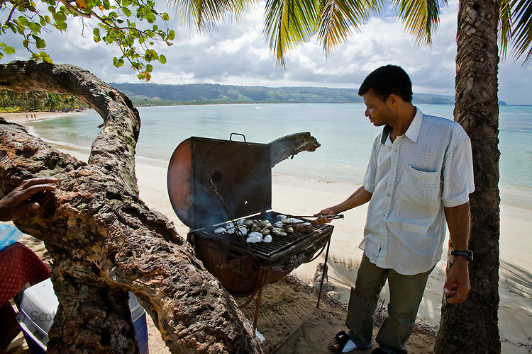 Local Dominican man grills potatoes and fresh fish on Playa Bonita and Coson, Samana, Domincan Republic