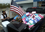 Joel Wallace posts an American Flag in his truck bed before he delivers supplies to refugees at Bay High School shelter after hurricane Katrina in Waveland, Mississippi.