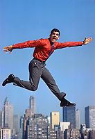 Van Heusen Shirt Ad (unpublished) for Grey Advertising. Model jumps on trampoline from roof of Pepsi building with New York skyline behind, 1963. Photo by John G. Zimmerman.