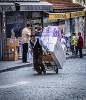 Urban Street Photograph of a man pulling his over stuffed dolly up a steep road in Istanbul Turkey.