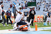 CHAPEL HILL, NC - OCTOBER 10: Dazz Newsome #5 of North Carolina is flipped upside down by Devin Taylor #24 of Virginia Tech after diving into the end zone for a 6-yard touchdown during a game between Virginia Tech and North Carolina at Kenan Memorial Stadium on October 10, 2020 in Chapel Hill, North Carolina.