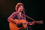 "A young Arlo Guthrie performs during a benefit concert with his band Shenandoah. The concert was held in Western Massachusetts in the 1970's . Arlo Davy Guthrie (born July 10, 1947 in Brooklyn, New York) is an American folk singer. Like his father Woody Guthrie Arlo often sings songs of protest against social injustice. Arlo's most famous work is ""Alice's Resturant Massacree"", a talking blues song that lasts for 18 minutes."