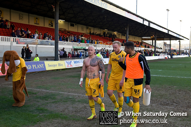 Newport County 1 Exeter City 1, 16/03/2014. Rodney Parade, League Two. Newport County finally return to the Football league after years of turmoil but a poor run of results has dented hopes of reaching the play-offs while Exeter City battle relegation. County players David Pipe, Lee Minshull and Rene Howe and a dejected looking Spytty the mascot make their way to the changing room after the 1-1 draw. Photo by Simon Gill