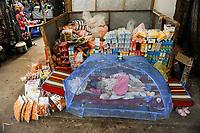 LAO PDR, Vientiane, market, girl sleeps under mosquito net / LAOS, Vientiane, Markt, Mädchen schläft unter Moskitinetz