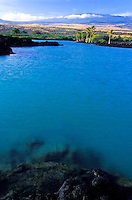 Beautiful blue waters of Kiholo Bay with its rocky lava island in the distance