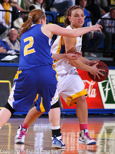 Ashlea Muckenhirn #42 of SDSU looks for a teammate while being pressured by Heather Davis #2 of UMKC during the first half of their game Saturday evening at Frost Arena. (Photo by Stephen Brua/Inertia)