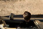 African Lion (Panthera leo) biologist, Xia Stevens, looking at male lion tracks on road, Kafue National Park, Zambia