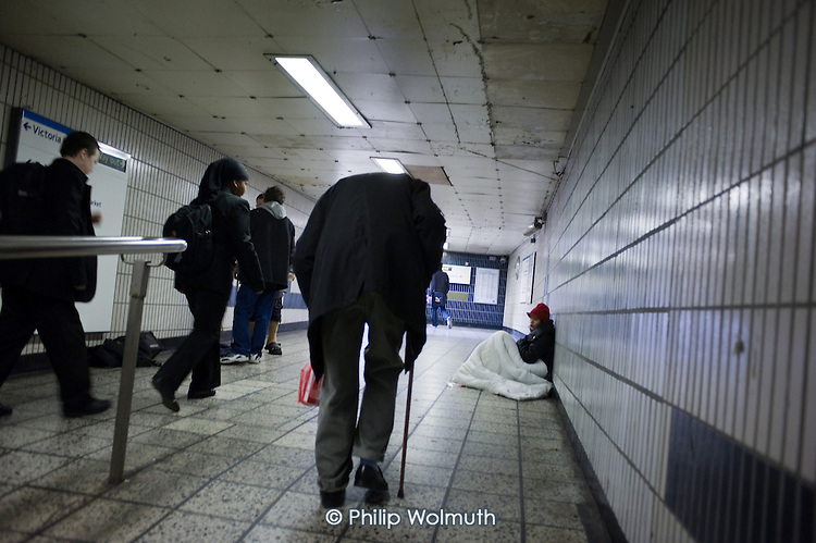 An elderly man with a walking stick walks past a homeless woman in a subway at Vauxhall underground station, London.