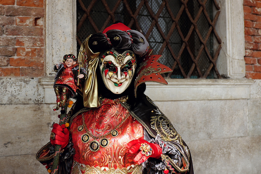 Man dressed in traditional mask and costume for Venice Carnival standing at Doge's Palace, Piazza San Marco, Venice, Veneto, Italy