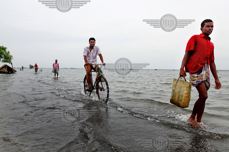 People walk and cycle through flood waters that have innundated the Satkhira district. Each year limited flooding helps to enrich the soil and create very fertile farm land. In turn, this results in a high population density on the flood plain. However, the low lying land is also prone to extreme flooding events that are very destructive and to both economy and life.