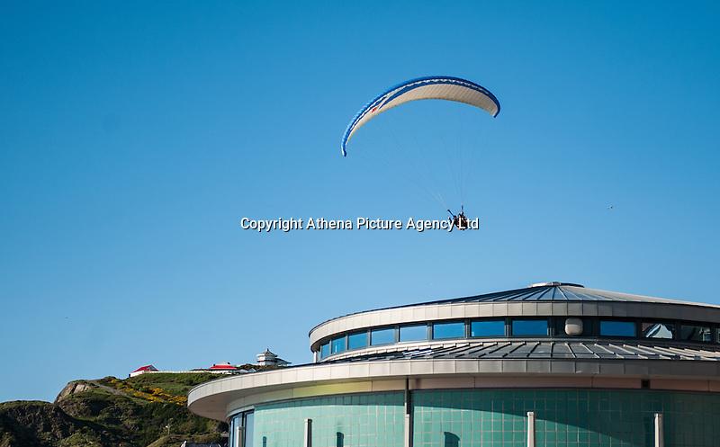 Aberystwyth, West Wales, UK Weather: A man paragliding over Aberystwyth promenade in Wales, UK