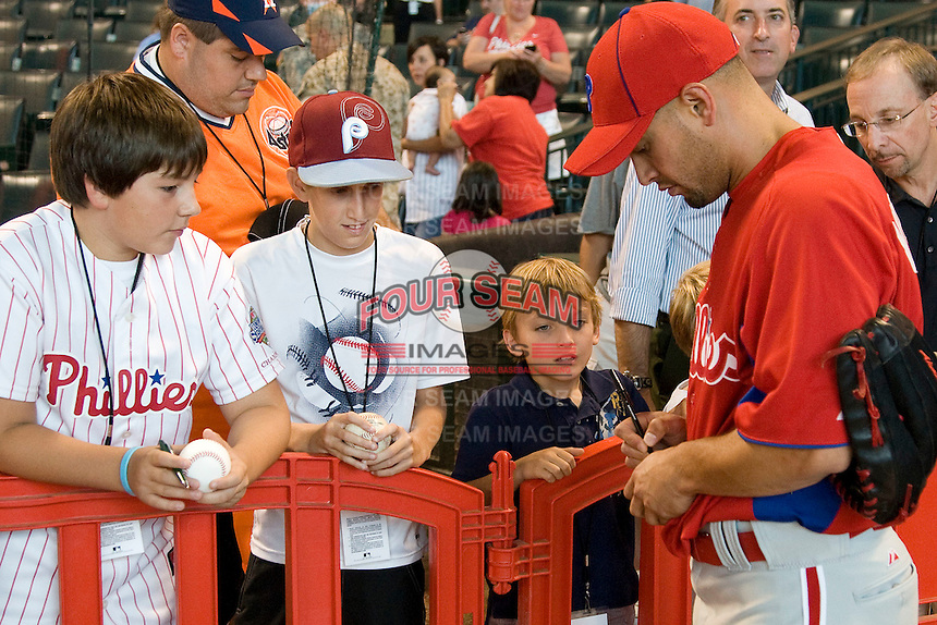 Philadelphia Phillies outfielder Shane Victorino #8 signs autographs for fans before the Major League Baseball game against the Houston Astros at Minute Maid Park in Houston, Texas on September 12, 2011. Houston defeated Philadelphia 5-1.  (Andrew Woolley/Four Seam Images)