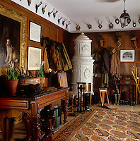 A Swedish ceramic stove stands in a corner of this panelled boot room which is decorated with a display of antlers and hunting trophies