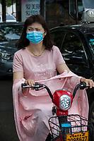 Suzhou, Jiangsu, China.  Friendly Woman on her Motorbike Wearing Breathing Mask.