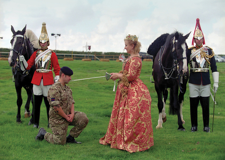 Queen of Lavenham, Jane Franzetta knights Trooper Ryan Hackett of the Household Cavalry. She is escorted by Corporal of Horse Jamie Elliot of the Blues & Royals, & Trooper Jacob Smith Longman of the Lifeguards.