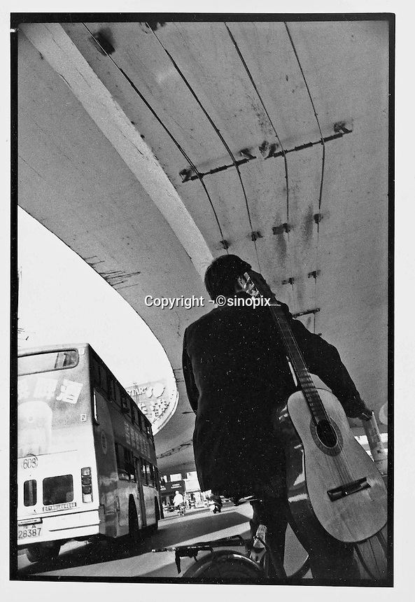 A man and his guitar ride under a concrete  overpass in Beijing...PHOTO BY WANG TONG / SINOPIX