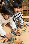 Education preschool 3 year olds two boys playing with floor puzzle