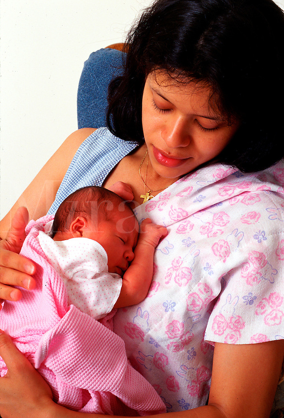 infant sleeps in her mothers arms.