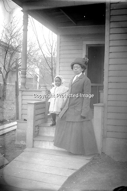 THE POSING PORCH. This modest porch was the setting of many John Johnson photographs of women and children, but none of the images yield a clue to the location or identities. The same youngster in the white winter coat is seen with two sisters on page in another image, and the trio appears with another woman on a different image. The various images of the trio suggest this child is younger brother to the two sisters. Is he standing here with one of his grandmothers?<br /> <br /> Photographs taken on black and white glass negatives by African American photographer(s) John Johnson and Earl McWilliams from 1910 to 1925 in Lincoln, Nebraska. Douglas Keister has 280 5x7 glass negatives taken by these photographers. Larger scans available on request.