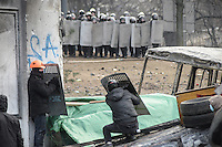 Rioters face a line of policemen using the Berkut shields stolen during the clashes .  Kiev. Ukraine