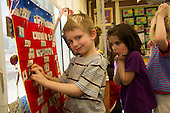 MR / Schenectady, NY. Zoller Elementary School (urban public school). Kindergarten inclusion classroom. Student (boy, 5) smiles as he selects activity from pocket chart for learning center time. Girl in background: 5. MR: Hol13, Coh2, Tor3. ID: AM-gKw. © Ellen B. Senisi.