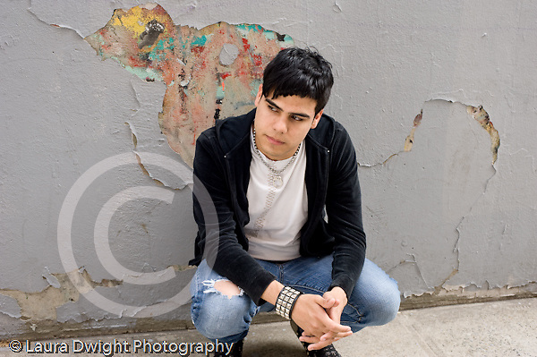 Education High School  senior students posing  outside school building male student alone squatting against wall with cracked and colorful paint looking to side moody serious horizontal