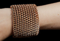 """A brass and bronze dragonscale weave chainmail bracelet seen on a pale-skinned arm up close.  The maille was made with 18ga 1/4"""" bronze and 19ga 11/64"""" jeweler's brass, and uses a gold tone slide clasp.  The view emphasizes how the flexible weave looks very different depending on the angle it's view from."""