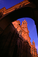 Arches frame an iron gate and turrets are reflected in sun and shadow at sunset of the Cathedral on the Plaza de Armas in Arequipa, Peru. The Spanish colonial architeture of the cathedral has survived the earthquake prone city.  It was constructed in 1656 but gutted by fire in 1844, then destroyed in the earthquake of 1868 but rebiult shortly thereafter.