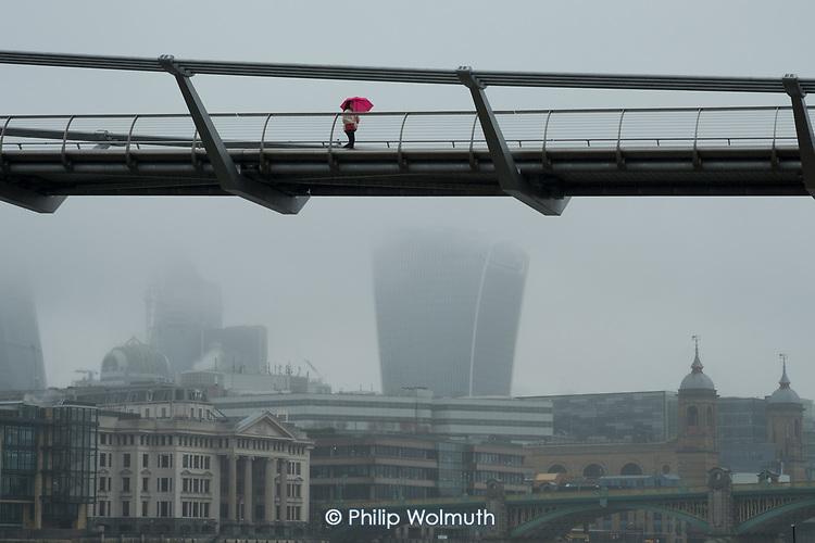 A woman with a pink umbrella crosses the Thames Millenium Bridge in heavy mist.
