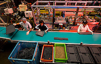 A group of workers inspect plastic items on an assembly line at SSI Schaefer plastic manufacturing in Charlotte, NC.