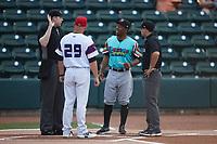 Llamas de Hickory manager Josh Johnson (1) and Winston-Salem Rayados manager Ryan Newman (29) meet with umpires Mitch Leikam (left) and Josh Gilreath (right) at Truist Stadium on July 6, 2021 in Winston-Salem, North Carolina. (Brian Westerholt/Four Seam Images)