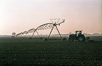 Motta Baluffi (Cremona). Trattore al lavoro in un campo al tramonto vicino a un impianto di irrigazione pivot --- Motta Baluffi (Cremona). A tractor plowing a field on sunset near a pivot irrigation system