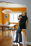 Jill Warner holds her dog Zoey in her Park Hill house that she shares with her husband, Erick Roorda.  They own the retro furniture and accessory store, Mod Livin' on East Colfax Ave, and their house is furnished from items that they sell in the store.   In their bright egg-yolk yellow dining room there is a danish modern table with vintage Cherner wood chairs and Philippe Starck's Louis Ghost chairs at each end.  A framed Pucci drawing, one of Jill's favorite artists, is on the wall in the corner.