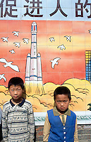 """China. Province of Henan. Village Xiaotan. Portrait of two young boys standing near a poster of a chinese space-rocket. The meaning of the poster is: """" practising family planning: promoting the all-round development of people"""". It is a confirmation of the strength of chinese science on future developments in towns, education and space-rocket. © 2004 Didier Ruef"""