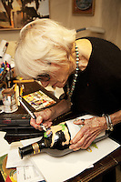 USA. California state. Napa valley. Margrit Biever Mondavi in her office at Robert Mondavi Winery, To Kalon Vineyard. She uses a knife to open the eyes of a naked Bacchus figure whom she painted on a Mondavi wine bottle. Margrit Biever Mondavi (born 1926 in Switzerland) is Vice President of Art and Culture at Robert Mondavi Winery which she joined in 1967. Under her direction, Robert Mondavi Winery developed original cultural and culinary arts programs. In 1980, she married Robert Mondavi and worked with him in many of his philanthropic activities. 16.12.2014 © 2014 Didier Ruef