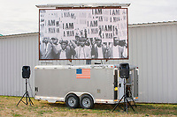"""A screen near the arrival area displays civil rights images of 1960s demonstrators hold """"I Am a Man"""" signs before the arrival of US President Donald Trump at a Make America Great Again Victory Rally in the final week before the Nov. 3 election at Pro Star Aviation in Londonderry, New Hampshire, on Sun., Oct. 25, 2020. Trump has frequently claimed he has done more for the Black community in the US than any other president with the """"possible exception"""" of Abraham Lincoln."""