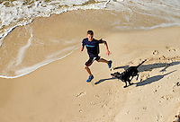 A teenage boy and his black lab dog run on the beach on Dauphin Island, Alabama, a barrier island located three miles south of the mouth of Mobile Bay in the Gulf of Mexico. This island, which is approximately 14 miles long and less than two miles wide, appears to have fully recovered from the impact of Hurricane Katrina (2005) and the BP Deepwater Horizon Oil Spill in 2010. Both events greatly reduced tourism income (fewer people came to the island) and local business owners say many establishments went out of business. Today they say they're looking forward to a rebounding tourism business.