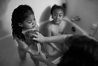 """Pat bathes with her adoptive daughter, Bella. Pat first adopted Bella, left, and later Nina, center, so the two girls would not be separated. To Nina, Pat is her mother and role model. Nina calls her biological parents """"the donors."""" (photo by Pico van Houtryve)"""