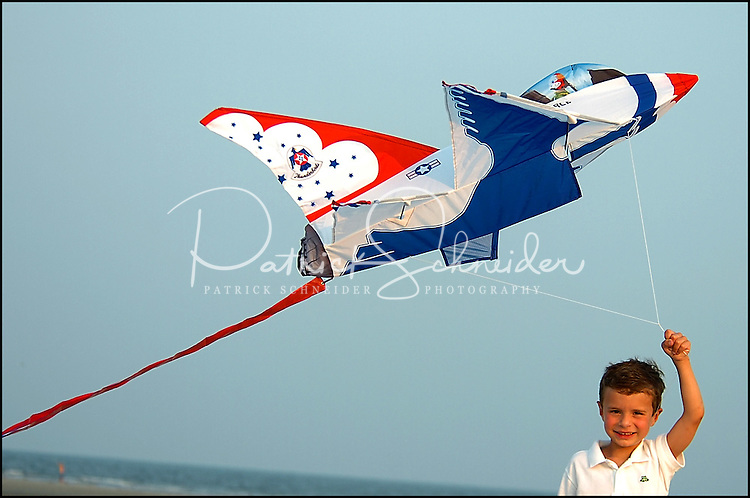 A young boy (model released) proudly holds onto the kite he is flying along an ocean beach on a windy evening. Photo taken along a South Carolina beach on the Atlantic Ocean, but could represent a beach scene anywhere.