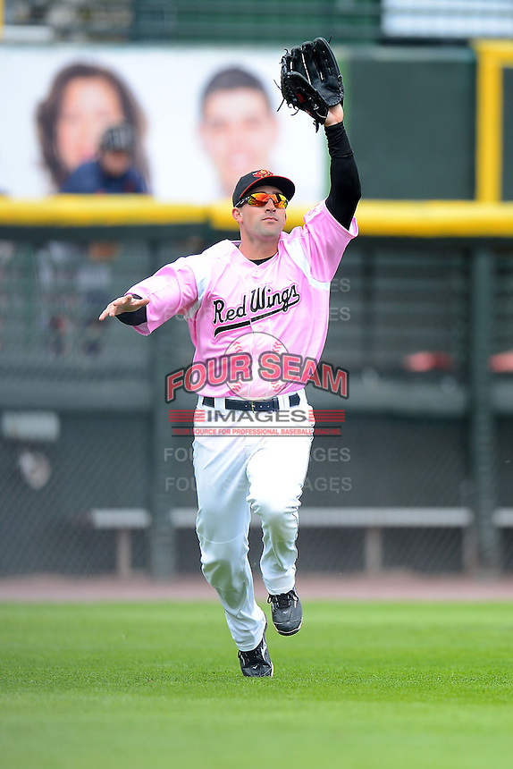 Rochester Red Wings outfielder Brian Dinkelman #12 fakes catching a fly ball to hold the runner during a game against the Columbus Clippers on May 12, 2013 at Frontier Field in Rochester, New York.  Rochester defeated Columbus 5-4 wearing special pink jerseys for Mother's Day.  (Mike Janes/Four Seam Images)